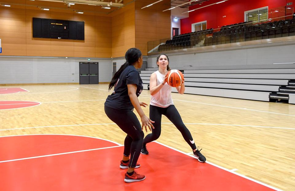 Two people playing basket ball in the high performance sports hall