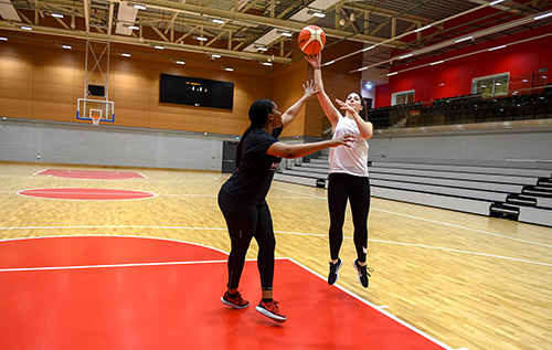Two women playing basketball together in the high performance sports hall at the Solent Sports Complex