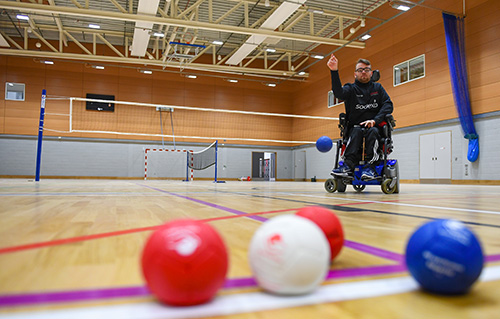 A man in a wheelchair playing sports in the multi-purpose sports hall at the Solent Sports Complex